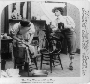 Woman in knickers smoking cigarette and looking at man doing laundry. Underwood and Underwood, c. 1901